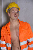 Handsome young construction worker with orange suit and hardhat Royalty Free Stock Photography