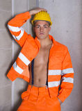 Handsome young construction worker with orange suit open on naked torso. Wearing yellow hardhat Stock Photo