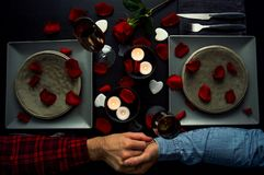 Handsome young couple having romantic diner holding hands. Top view. Candles, flowers and wine stock photo