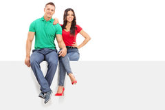 Handsome young couple sitting on a blank panel Stock Photo