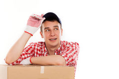Handsome young courier with brown box Royalty Free Stock Image