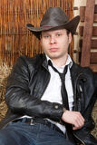 Handsome young cowboy. Glam cowboy in leather jacket in the rural interior is sitting on a haystack Royalty Free Stock Photos