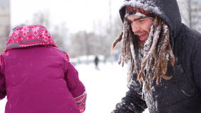 Handsome young dad and his little cute daughter are having fun outdoor in winter. Enjoying spending time together while stock video