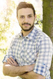 Handsome young dark-haired man standing by a tree Royalty Free Stock Photos