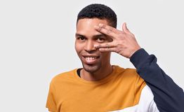 Handsome dark skinned man hiding his face with palm and show his eye. Studio portrait of young male covering his face by hand stock photography