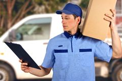 Handsome young delivery man carrying carton box royalty free stock images