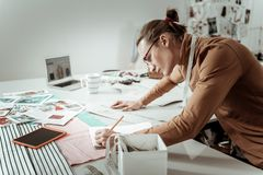 Handsome young designer from a fashion school in eyeglasses noting down measurements. Useful notes. Handsome young designer from a fashion school wearing royalty free stock images