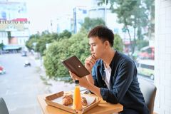 Handsome young designer writes creative graphic notes and making. Sketch in notebook while sitting at wooden table in coffee interior. Thoughtful man writing stock photos