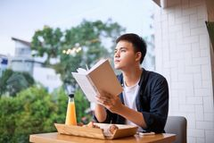 Handsome young designer writes creative graphic notes and making sketch in notebook. While sitting at wooden table in coffee interior. Thoughtful man writing royalty free stock photography