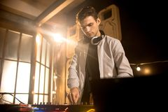 Handsome Young  DJ Playing in Club. Low angle portrait of trendy young DJ playing music using mixer and looking at laptop screen in  night club party, copy space Royalty Free Stock Photography