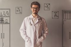 Handsome young doctor. In medical coat and eyeglasses is looking at camera and smiling, on gray background with drawn office furniture Stock Photography