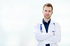Handsome young doctor in office Stock Images
