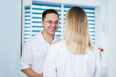 Handsome young doctor is talking with his beautiful female assistant, standing in waiting room of the clinic stock photos