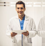 Handsome young doctor. In white coat is holding a digital tablet, looking at camera and smiling while standing in hospital corridor Royalty Free Stock Photos
