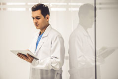 Handsome young doctor. In white coat is using a digital tablet while standing in hospital corridor Stock Image