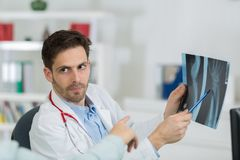 Handsome young doctor at work in office. Handsome young doctor at work in his office Stock Image