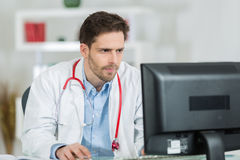 Handsome young doctor at work in office Royalty Free Stock Images