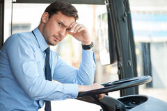 Handsome young driver is sitting at steering wheel Royalty Free Stock Photos
