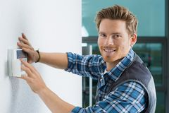 Handsome young electrician repairing intercom royalty free stock image