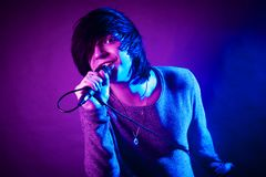 Handsome young emo guy singing. The handsome young emo guy is singing in microphone on purple and blue concert lighting royalty free stock photography
