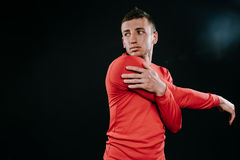 Handsome young European man wearing red sportswear and stretching his arms after a hard workout in dark background. Powerful hands. Caucasian sportsman wearing Stock Image