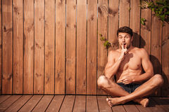 Handsome young excited man sitting and showing silence gesture. Over wooden background Stock Photo