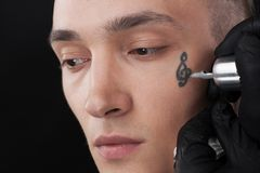 Handsome young face getting tattoo. Stock Images