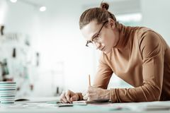 Handsome young fair-haired designer from fashion school making sketches. Sketches. Handsome young fair-haired designer from fashion school looking busy while stock images