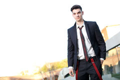 Handsome young fashion male model. Wearing shirt and red braces posing outdoors Royalty Free Stock Photos