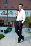 Handsome young fashion male model. Handsome young business fashion male model wearing shirt and red braces posing outdoors Stock Photos