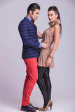 Handsome young fashion man embracing his girlfriend. Side view of a handsome young fashion men embracing his girlfriend while she is looking at the camera royalty free stock images