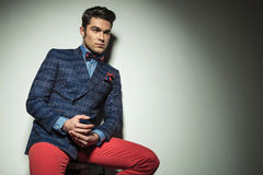 Handsome young fashion man sitting on a chair. Royalty Free Stock Images