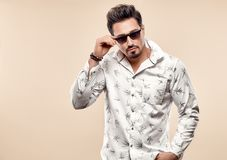 Handsome young Fashion man in Trendy Sunglasses. Sporty Confident Brunette Bearded guy in white shirt, Stylish Hairstyle, Summer Elegant Outfit. Studio fashion royalty free stock photo