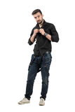 Handsome young fashion model buttoning black shirt Stock Photos