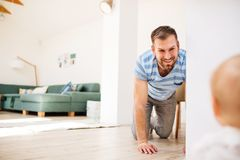 Young father with a baby son at home, having fun. Handsome young father with a baby son at home, crawling on the floor Royalty Free Stock Photography