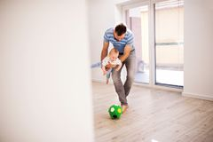 Young father with a baby son at home playing with a ball. Handsome young father with a baby son at home, playing with a ball stock image