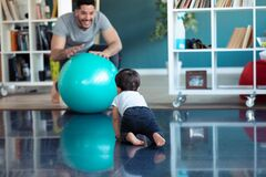 Handsome young father with his baby playing together and having fun with the ball at home