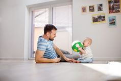 Young father playing with an unhappy baby son at home. Handsome young father playing with an unhappy baby son at home Stock Photography