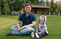 Handsome young father sitting with his 9 months old son on grass Royalty Free Stock Image