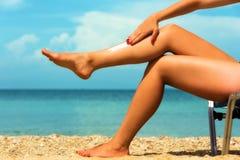Handsome young female, applying sun tan cream Stock Image