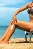 Handsome young female, applying sun tan cream Royalty Free Stock Image