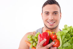 Handsome young fit guy prefers healthy eating. Attractive man is holding fruits and vegetables in his hands greedily. He is looking at the camera and smiling Stock Image