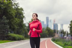 Young fitness woman running in the city park. Handsome young fitness woman running in the city park in the morning Royalty Free Stock Images