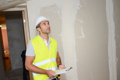 Handsome young foreman supervising a house renovation contruction site Royalty Free Stock Image
