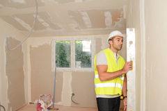 Handsome young foreman supervising a house renovation contruction site. Handsome young foreman supervising house renovation contruction site stock photo