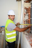 Handsome young foreman supervising a house renovation contruction site Stock Photos