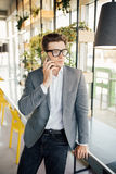 Handsome young freelance business man speak on phone in modern office Royalty Free Stock Photos
