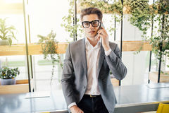 Handsome young freelance business man speak on phone in modern office Royalty Free Stock Image