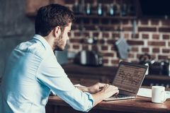 Handsome Young Freelance Man Typing on Laptop. Smiling Man Working and is Using Laptop while Making Notes on Paper. Freelance Worker. Happy Businessman Work royalty free stock images
