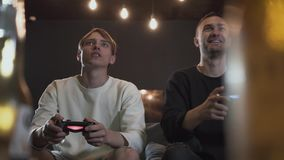 Handsome young friends having fun on evening playing video games drinking beer with excellent mood in modern loft club. Happy young friends having fun on evening stock video footage